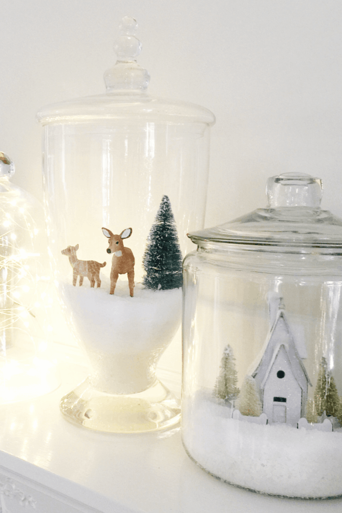 homemade christmas gift ideas, two glass containers filled with fake snow, with two deer and a pine tree, a church and some small tree figurines