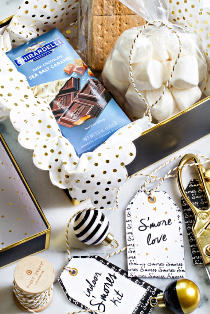 a black and gold box with white and gold wrapping paper inside, with chocolate and biscuits and a bag of white marshmallows, near festive labels and scissors and small christmas ornaments