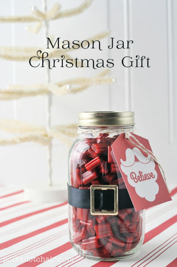 family christmas gifts, a mason jar filled with red candy, a black belt with yellow buckle, and a red festive card, white and red surface with fake white christmas tree in the background