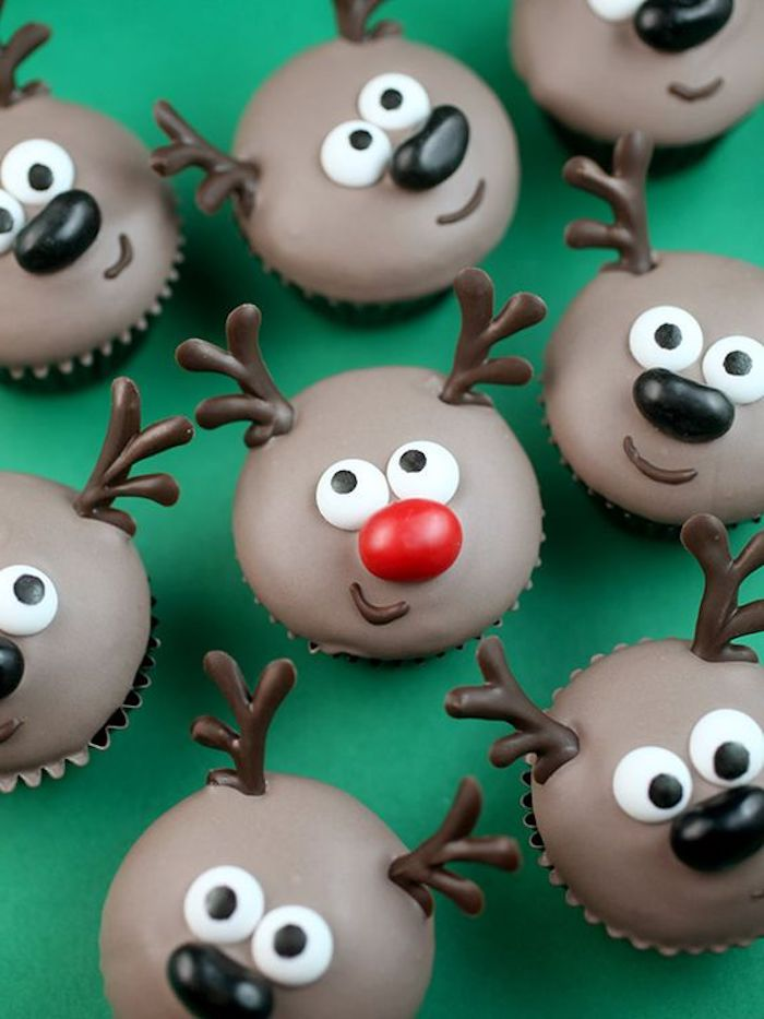 batch of cupcakes with brown frosting, iced with chocolate and made to look like reindeer, middle one has red nose