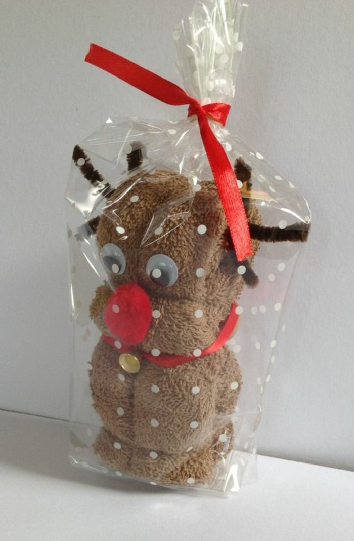 brown fluffy towel made to look like a reindeer, with red collar and a golden bell, googly eyes, brown wire antlers and red pom-pom nose stuck on it, in clear plastic wrapping paper tied with red ribbon