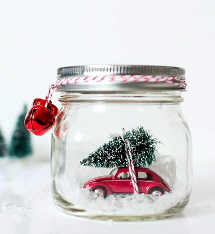homemade christmas gift ideas, little red car toy with snowy christmas tree figurine tied on its roof, fake snow and white and red string, inside a clear jar with screw cap, two red bells