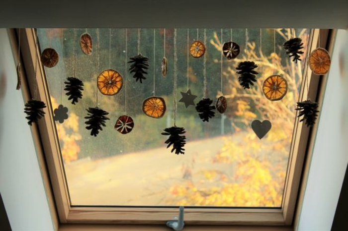 a window decorated with dried orange slices and pine cones, hanging on strings, with heart star and flower shapes