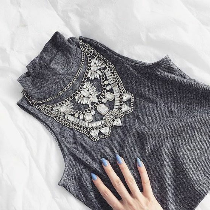 close up of sleeveless grey turtleneck top, with large and elaborate diamante and silver necklace, female hand with pastel blue nail polish