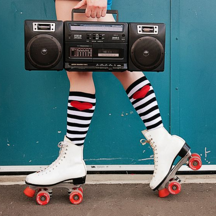 close up of legs wearing retro white skates with red wheels, black and white stripped bellow the knee socks with red hearts, hand holding black retro stereo or boombox, blue background and pavement