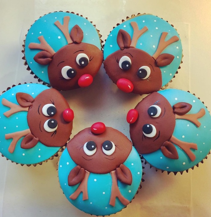 five cupcakes with brown, blue and red fondant icing, made to look like rudolph the reindeer, placed in a circle