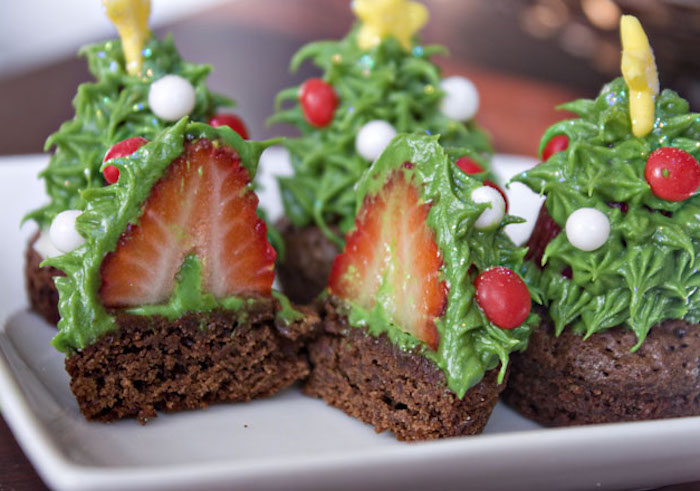 several chocolate brownies, with green frosting made to look like x-mas tree, decorated with white and red candies and little yellow stars, one brownie cut in half to reveal strawberry in icing