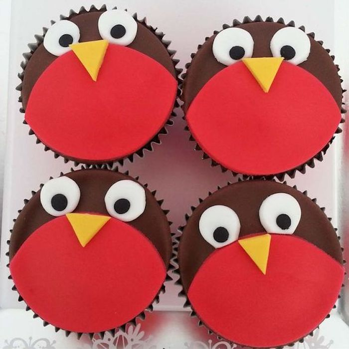four cupcakes decorated with red and brown fondant, with yellow white and black details, made to look like birds