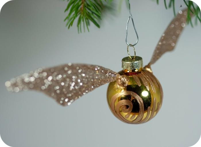 a yellow tree ornament painted with gold paint, with glittering wings and a golden cap, hanging from christmas tree on a metal hook