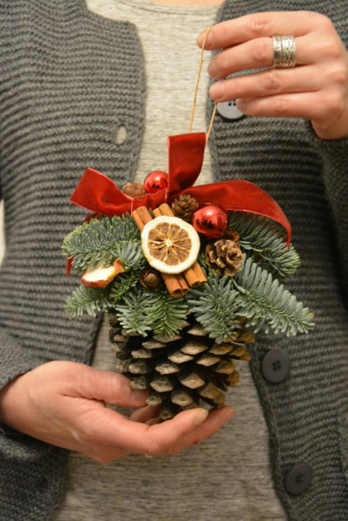 woman in grey sweater and light grey top, holding a christmas ornament made from a big pine cone, decorated with cinnamon sticks pine twigs and dried fruit, small ornaments and red ribbon