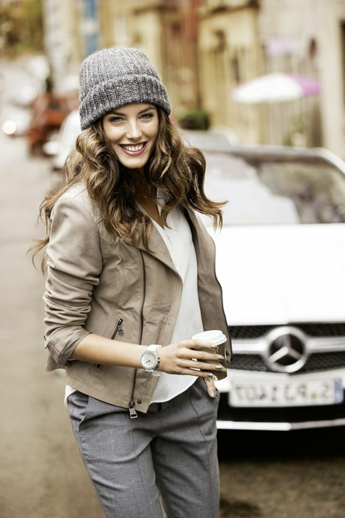 smiling woman with curled brown hair and grey beanie hat, wearing pale grayish-brown leather jacket, white top and grey formal trousers