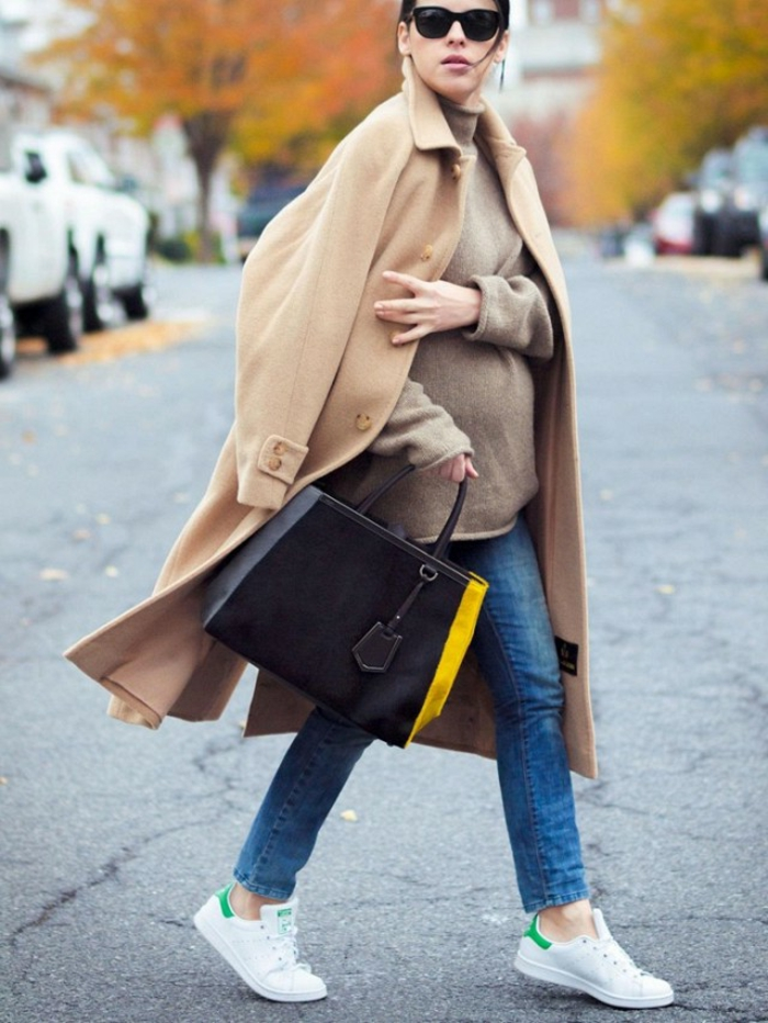 soft and long camel brown coat, worn by mother-to-be with blue jeans and large mink-colored sweater, sunglasses and black bag with yellow stripe, white sneakers with green details