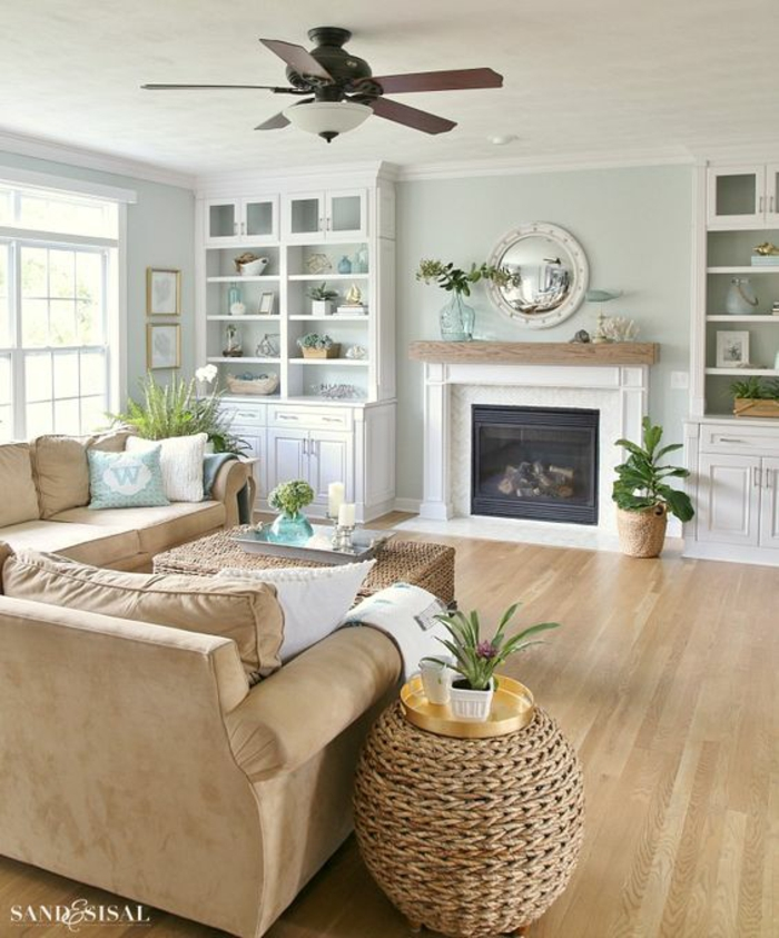 living room paint colors, pale blue walls and white ceiling, lamp with ceiling fan, pale camel-colored sofa, two wicker tables and two white cupboards, fireplace and wooden floors