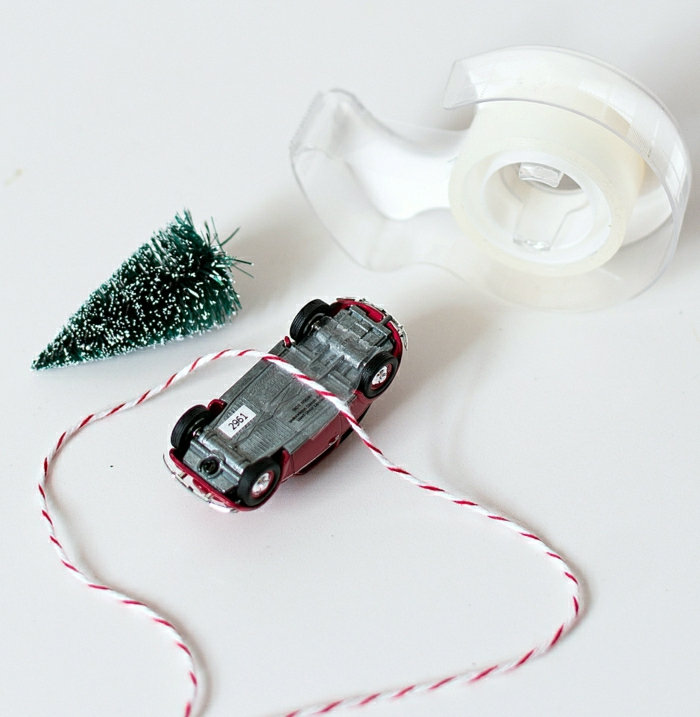 homemade christmas gift ideas, sticky tape on white stand, red car toy turned on its back, a small snowy christmas tree ornament, some white and red string