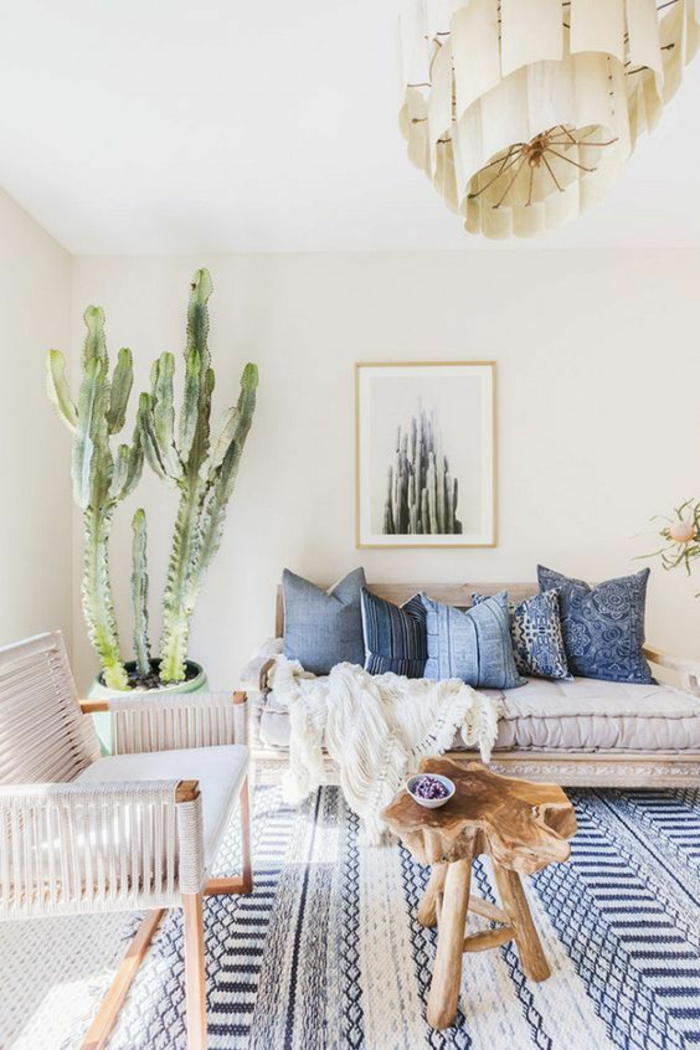 living room color schemes, cream walls and white ceiling, blue and cream carpet, off-white sofa with five blue pillows, white chair with wooden legs, large cactus plant in pot