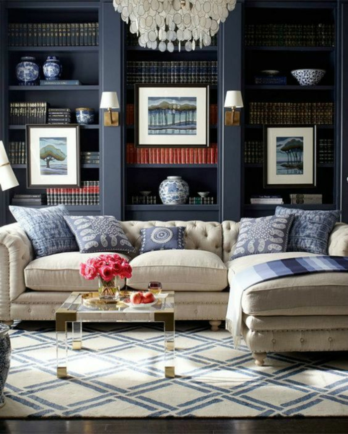 dark blue or black in-built library shelves, light cream sofa with five blue and cream pillows and blanket, small coffee table with flowers and decorations, cream and dark blue carpet
