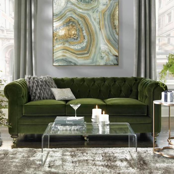 lush green sofa with two grey cushions, clear glass table with two lit candles, fluffy grey carpet, grey wall with yellow green and grey painting, windows with grey curtains