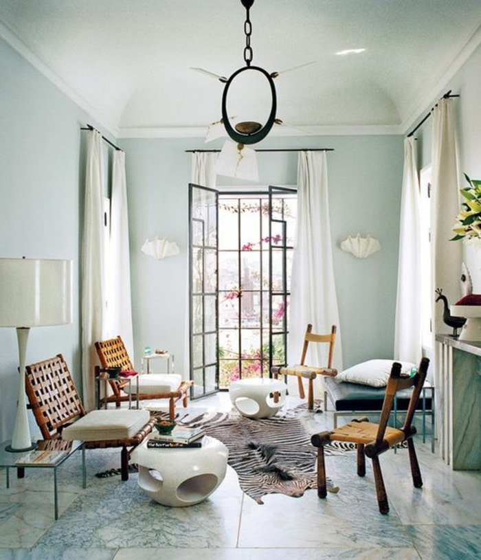 room with pale blue walls, windows and cream curtains, four wooden chairs and two small white tables, blue and cream tiled floor, white lamp and unusual chandelier, striped animal hide on floor