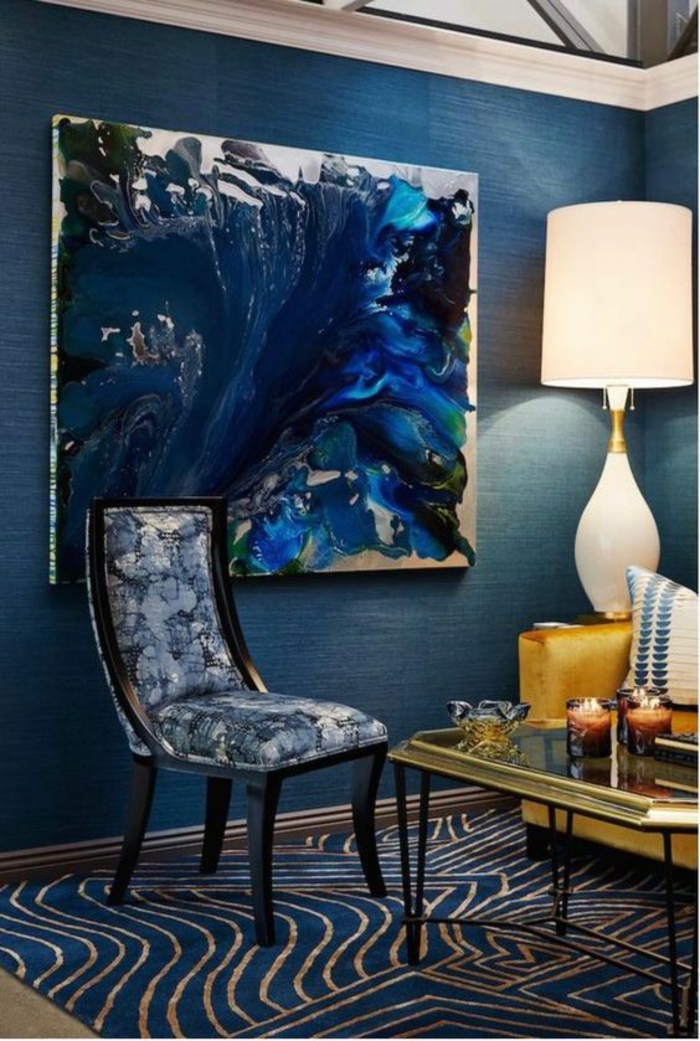 paint colors for living room, dark blue walls, blue and cream carpet, lighter blue and cream chair with black details, white lamp and glass table with gold details, large dark blue abstract painting