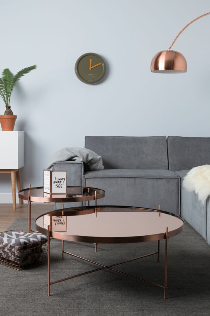 pale blue wall, grey sofa and white cupboard with wooden legs and potted plant, copper colored metal tables, grey carpet and wooden floor, olive green wall clock, grey blankets and cream sheep hide