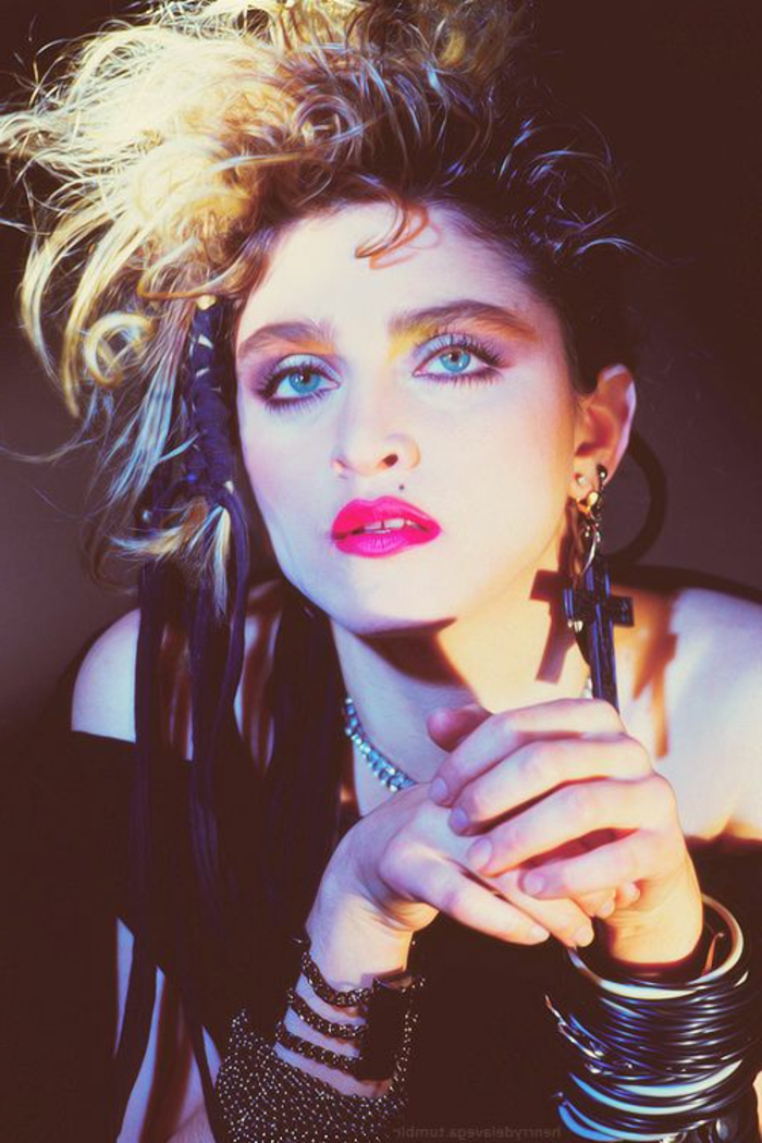 80s fashion, madonna with short messy blond hair, a lot of bangles bracelets and earring with big black cross, hair ornament with purple tassels