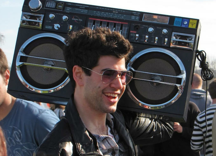 smiling man with gelled up wavy brown hair, aviator sunglasses and black leather jacket, carrying a retro stereo boombox, crowd in background
