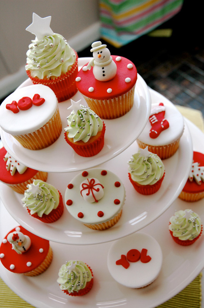 cupcakes of different sizes, with white and red fondant icing and pale green creamy frosting, on several differently sized white stacked plates