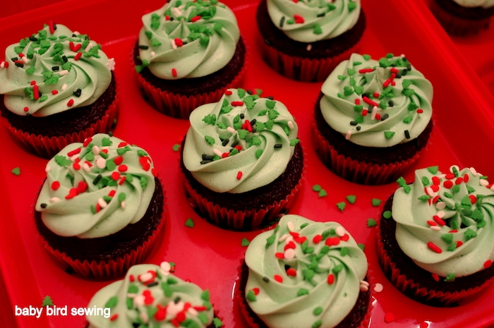 chocolate cupcakes images, nine chocolate cupcakes with green icing, decorated with white, green and red sprinkles, on red cupcake mould