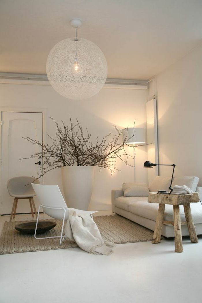 living room paint colors, cream colored walls, white sofa and chair, small rough wooden chair, big white vase with dry tree branches, cream chunky rug and cream chair
