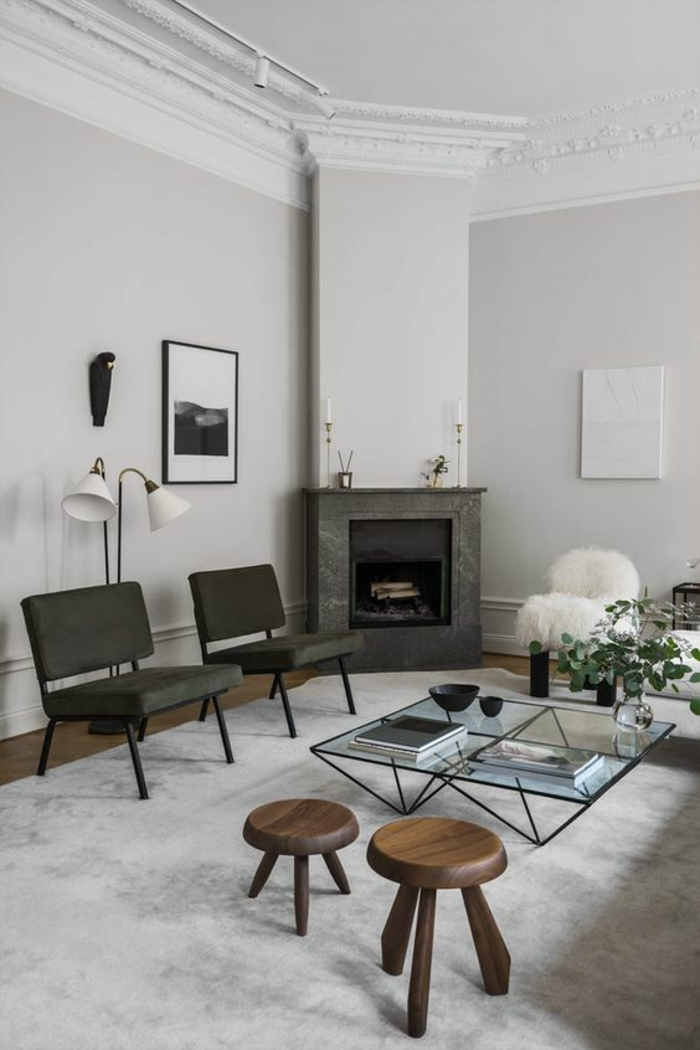 living room color schemes, pale grey walls and white ceiling with white plaster details, grey fireplace and two grey chairs, two small round wooden chairs, clear glass table with black metal legs and details