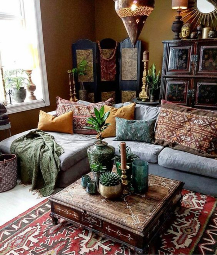 living room color schemes, brown walls and a colorful persian carpet, pale grey sofa, yellow and patterned cushions, eastern wooden furniture and ornaments, plants lamps and candles