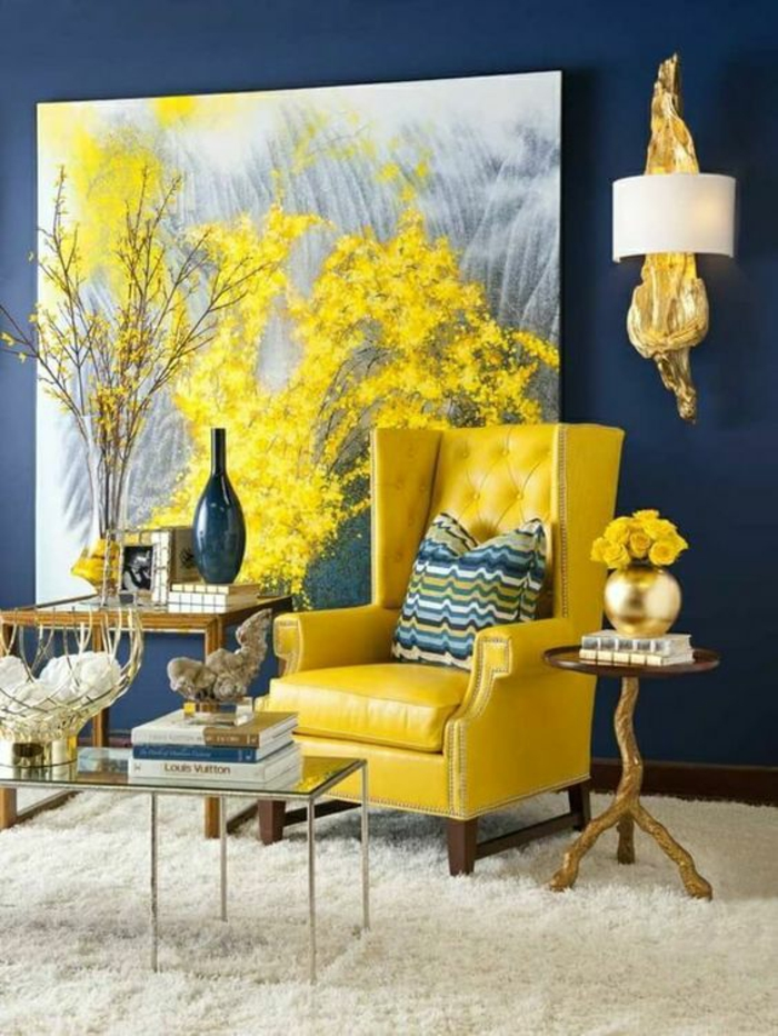 paint colors for living room, fluffy cream carpet, yellow leather chair with green and blue striped cushion, large yellow and grey painting, dark blue wall and gold and white lamp, three different tables