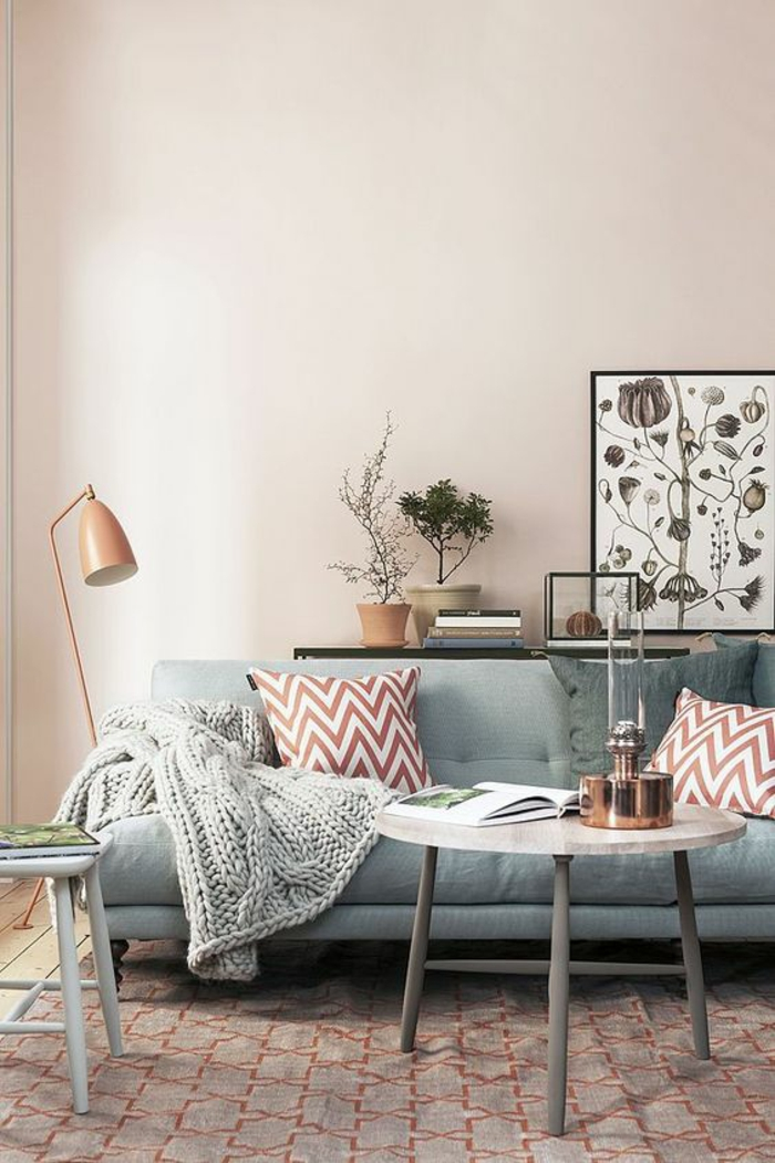 color schemes for living rooms, pale pastel pink wall, pale pastel blue sofa, two dark brownish-red striped cushions, grey chunky knit blanket, pale round coffee table with grey legs