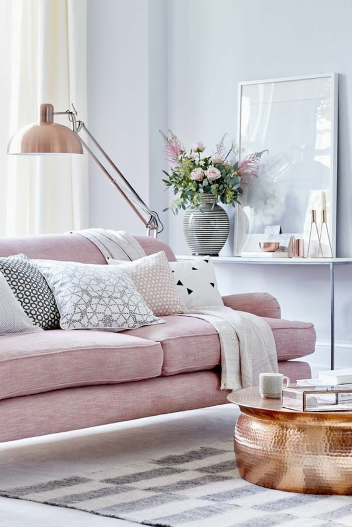 room with pale lilac walls and pale salmon pink sofa, five differently colored cushions, rose gold metal lamp, copper colored round metal table, chequered grey and cream rug