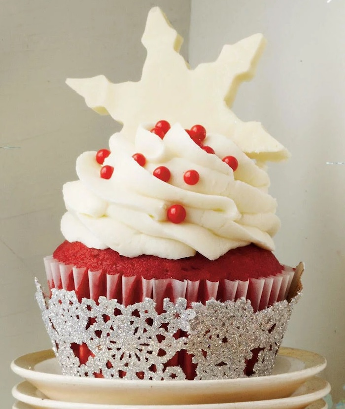 close up of red velvet cupcake with white frosting, decorated with big white snowflake shape and red pearls
