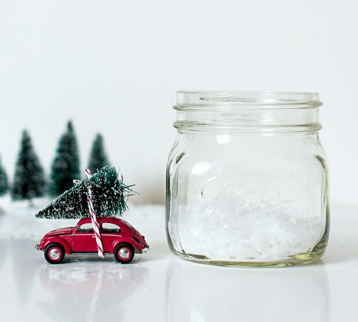 homemade christmas gift ideas, empty clear bell jar, near a red car toy with miniature christmas tree tied on its roof, with red and white string