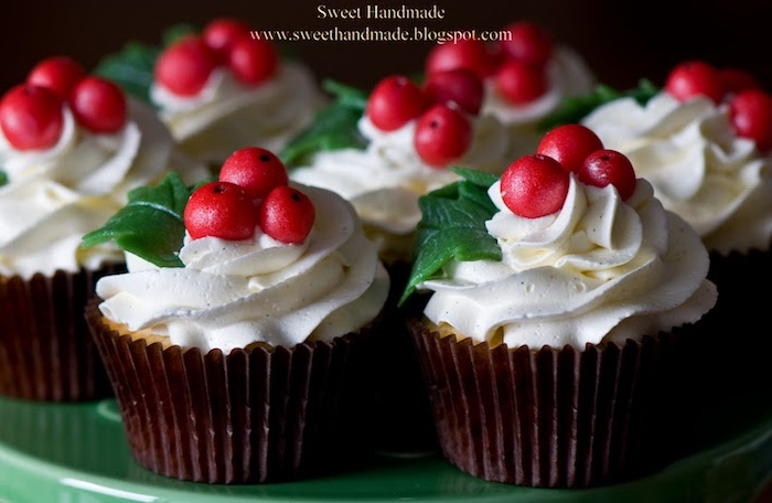 a batch of cupcakes in brown wrappers, with white icing decorated with cranberry berries and leaves, on green dish