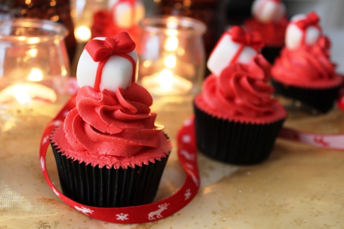 holiday cupcakes, a few cupcakes with black wrappers and red creamy icing, decorated with white and red fondant present shapes, candles and festive red ribbon