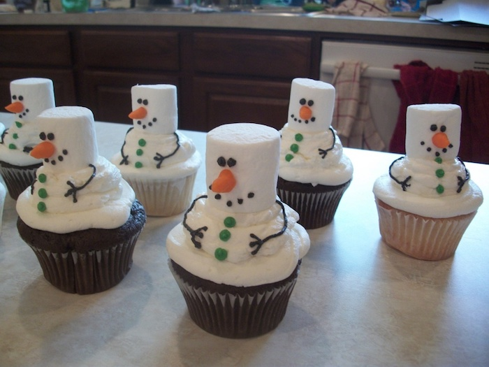 a batch of chocolate and vanilla cupcakes, decorated with marshmallow creme and actual marshmallows, made to look like snowmen with icing and fondant