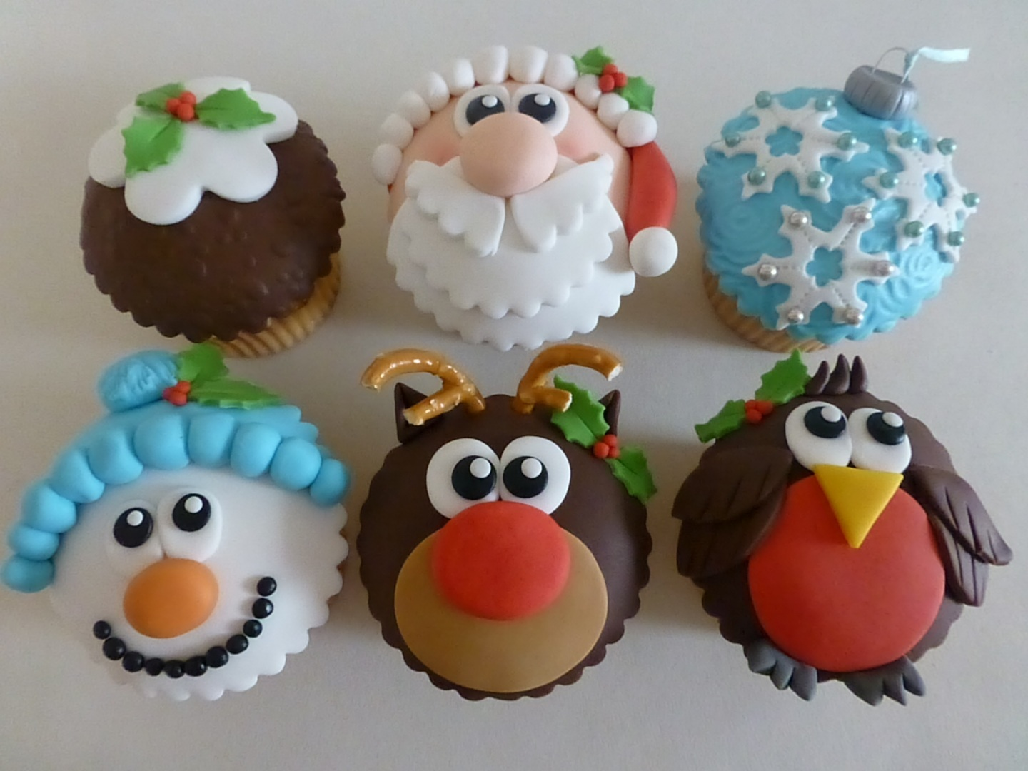 six cupcakes decorated with brown, white red pink and blue fondant icing, shaped like santa and reindeer, snowman and bird, christmas pudding and ornament