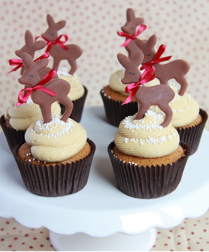 six cupcakes in brown wrappers, with light yellow frosting, decorated with chocolate deer shapes, with red bows around their necks