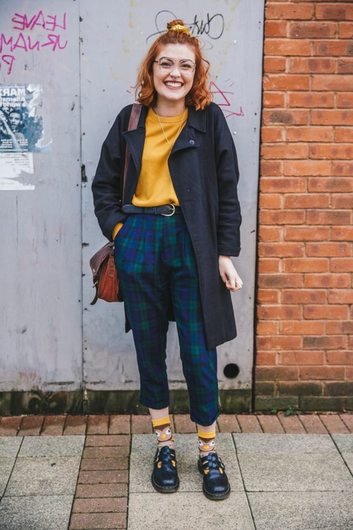 smiling woman with curly ginger hair and a top knot, navy blue coat over mustard yellow jumper, cropped blue and green tartan trousers, brown bag and owl socks