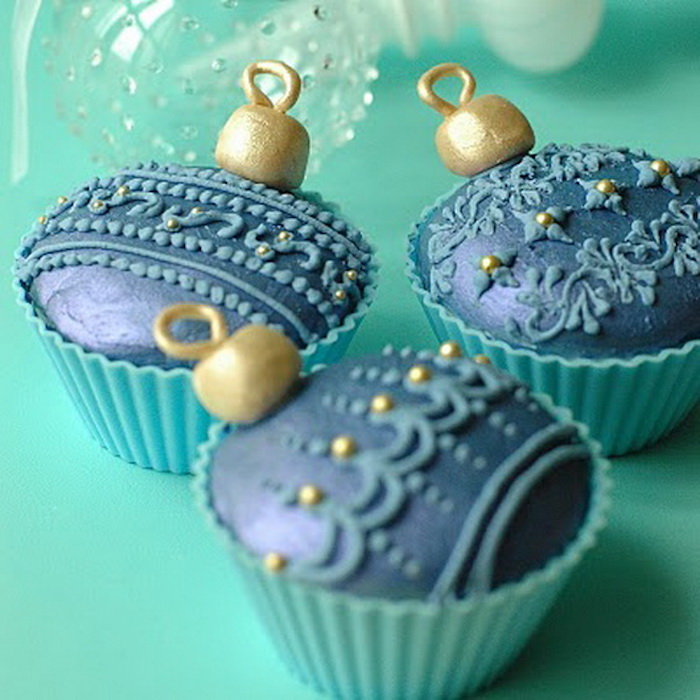 three cupcakes in pale blue moulds, with dark blue and gold icing, made to look like christmas ornaments, light turquoise background