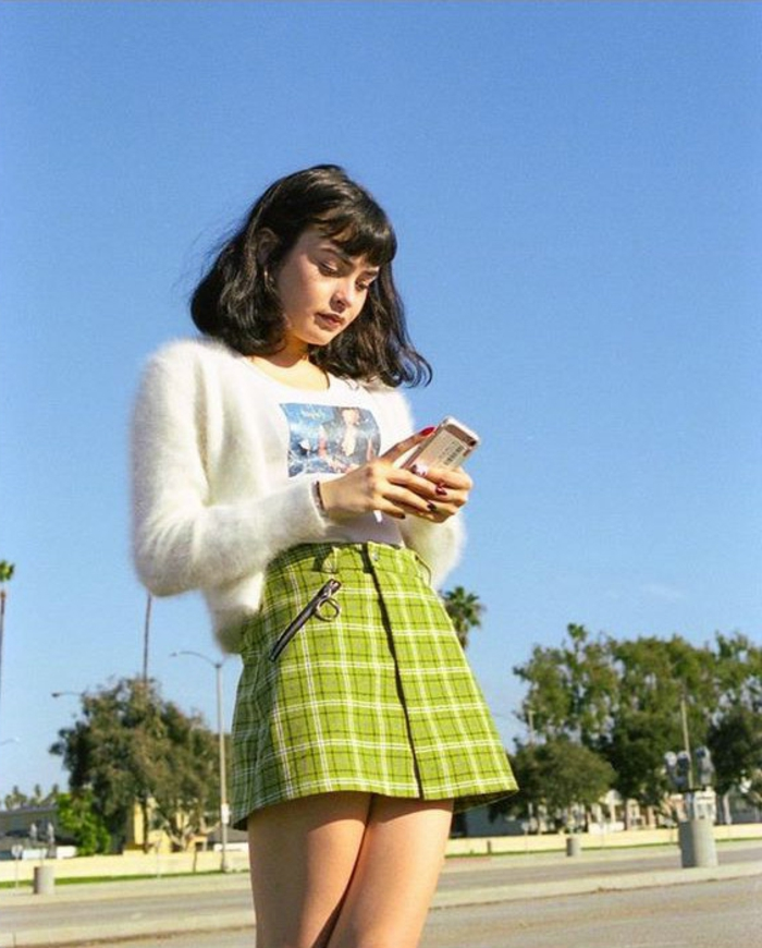 throwback thursday outfits, girl with shoulder-length black hair and bangs, wearing a short tartan lime green mini skirt, white t-shirt and a white fluffy cardigan