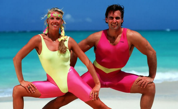80's fashion for men, woman and men working out on beach, wearing neon colored yellow and pink bodysuits, pink cropped sport leggings and colorful headband, azure blue sea and sky in background