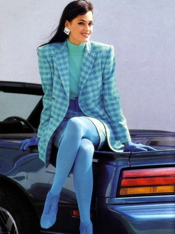 80s fashion, young smiling brunette with big square earrings, sitting on a blue retro convertible car, wearing a checked blue skirt suit with oversize blazer, opaque blue tights blue shoes and blue gloves