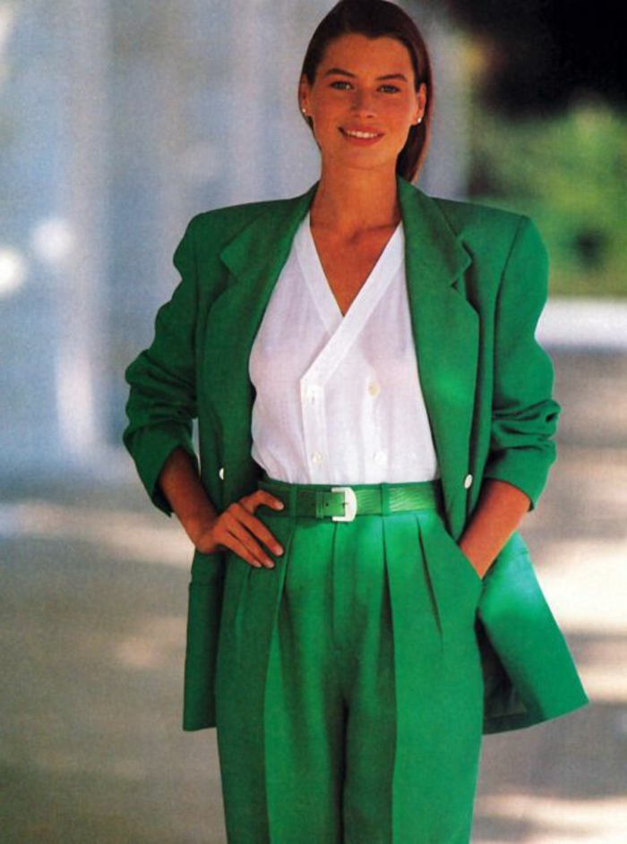 throwback outfits, smiling brunette woman in green 80s suit with white shirt, over-sized blazer and baggy pants, hand in pocket and hand on hip