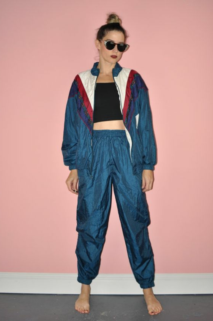 what did people wear in the 80s, woman with top knot and dark retro sunglasses, wearing a shiny windbreaker, track bottoms and black crop-top, barefoot on grey floor with pink background