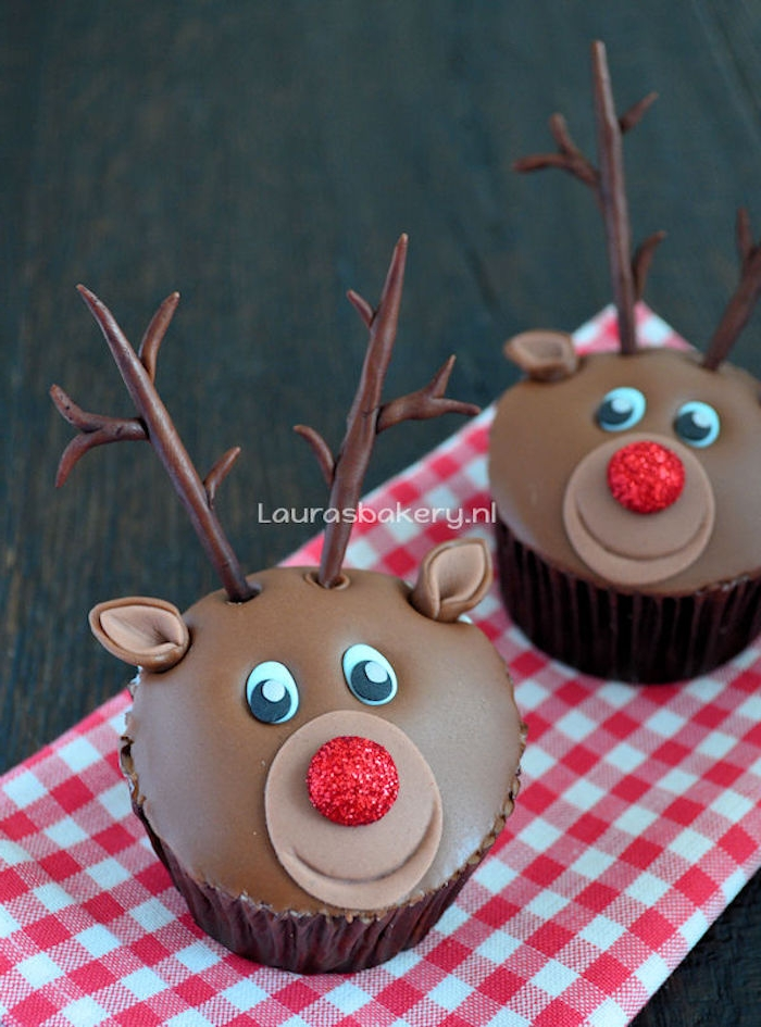 two cupcakes with smooth chocolate icing, made to look like reindeer, with fondant antlers and ears, and red sparkly noses, on red and white checkered cloth