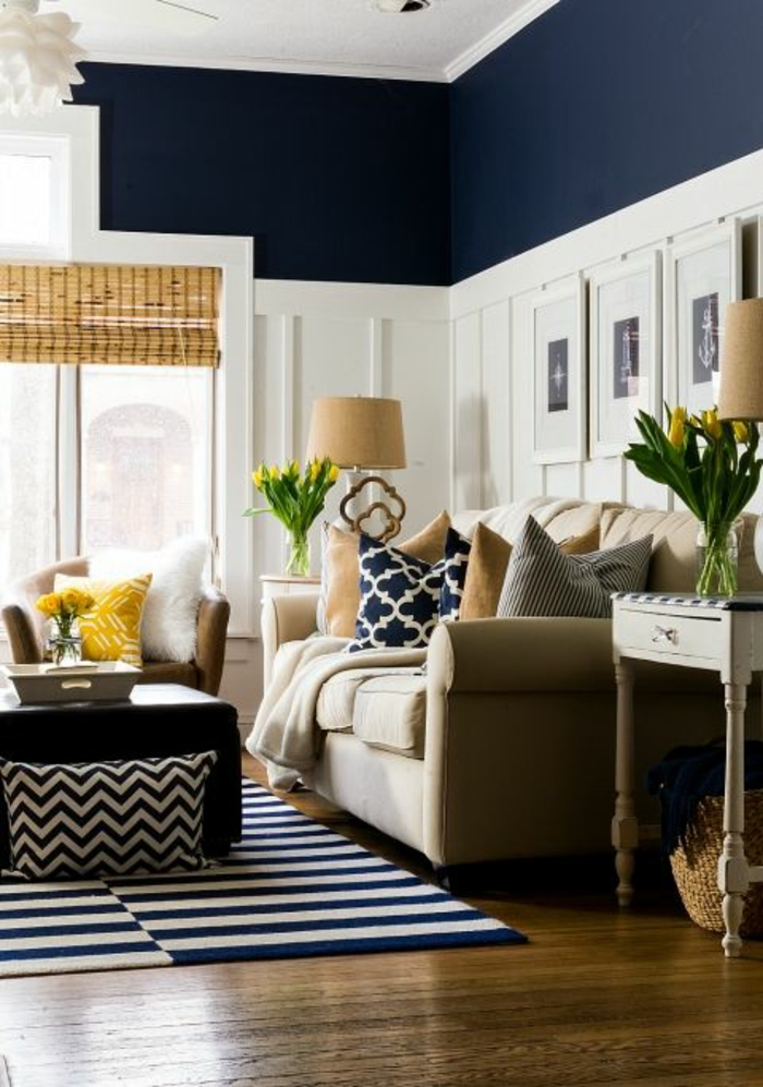 two tone living room walls, dark navy blue and white wall with plaster details, dark blue and white striped rug, cream colored sofa with yellow and blue cushions, brown chair with yellow and white cushions